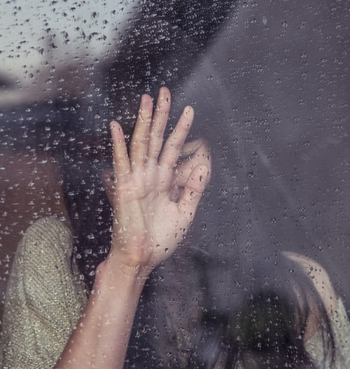 Woman upset looking out of a rainy window