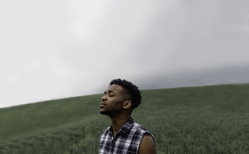Person on a hill with eyes closed